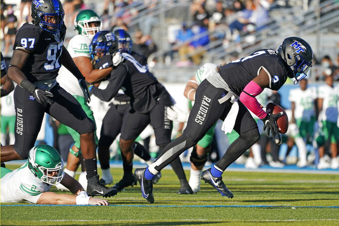 Middle Tennessee safety Gregory Grate Jr. (3) picks up a fumble by North Texas quarterback Austin Aune (2) in the first half of an NCAA college football game Saturday, Oct. 17, 2020, in Murfreesboro, Tenn. Grate ran the ball in for a touchdown. (AP Photo/Mark Humphrey)