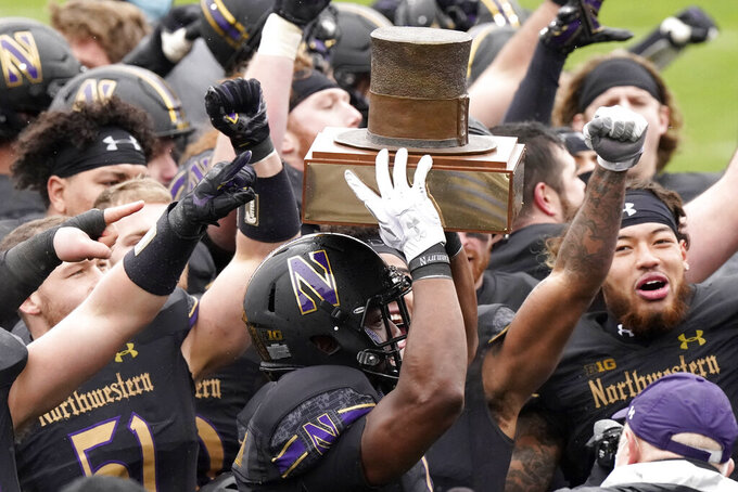 Northwestern running back Jesse Brown, center, celebrates with teammates as he holds the Land of Lincoln Trophy after Northwestern defeated Illinois 28-10 in an NCAA college football game in Evanston, Ill., Saturday, Dec. 12, 2020. (AP Photo/Nam Y. Huh)