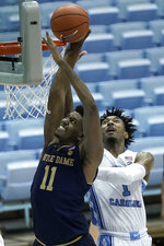 Notre Dame forward Juwan Durham (11) drives to the basket while North Carolina guard Leaky Black (1) defends during the second half of an NCAA college basketball game in Chapel Hill, N.C., Saturday, Jan. 2, 2021. (AP Photo/Gerry Broome)
