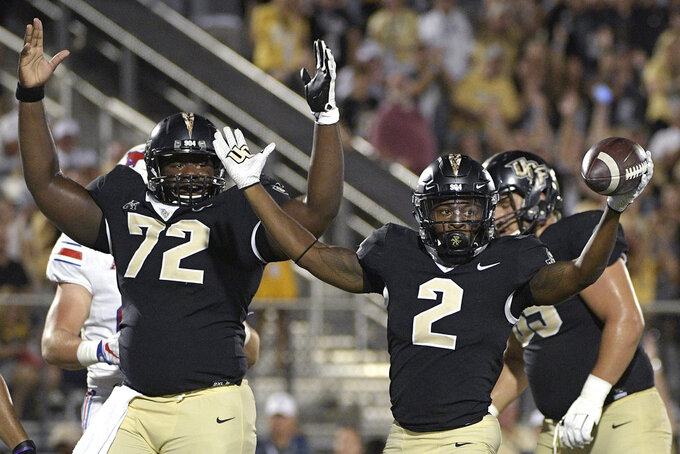 Central Florida offensive lineman Jordan Johnson (72) celebrates with running back Otis Anderson (2) after Anderson rushed for a 4-yard touchdown during the first half of an NCAA college football game against SMU Saturday, Oct. 6, 2018, in Orlando, Fla. (AP Photo/Phelan M. Ebenhack)