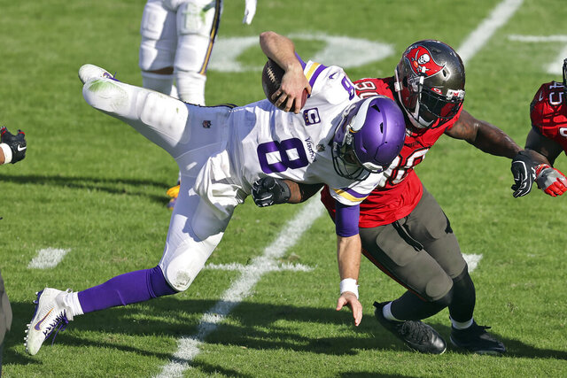 Minnesota Vikings quarterback Kirk Cousins (8) gets upended by Tampa Bay Buccaneers outside linebacker Jason Pierre-Paul (90) during the second half of an NFL football game Sunday, Dec. 13, 2020, in Tampa, Fla. (AP Photo/Mark LoMoglio)