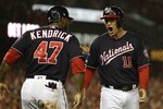 Washington Nationals' Ryan Zimmerman reacts with Howie Kendrick after scoring during the first inning of Game 4 of the baseball National League Championship Series against the St. Louis Cardinals Tuesday, Oct. 15, 2019, in Washington. (AP Photo/Jeff Roberson)