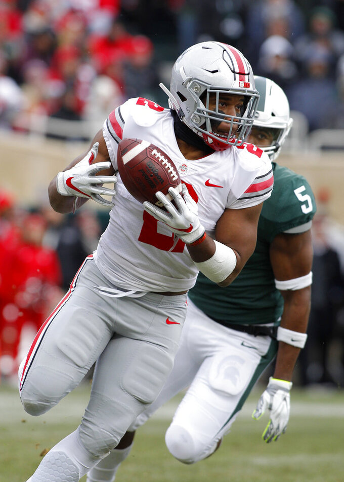 Ohio State's J.K. Dobbins (2) catches a pass in front of Michigan State's Andrew Dowell (5) during the first quarter of an NCAA college football game, Saturday, Nov. 10, 2018, in East Lansing, Mich. (AP Photo/Al Goldis)