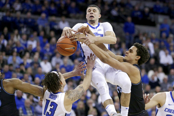 Creighton's Christian Bishop (13) and Marcus Zegarowski, center, and Villanova's Jeremiah Robinson-Earl (24) go for a rebound during the first half of an NCAA college basketball game in Omaha, Neb., Tuesday, Jan. 7, 2020. (AP Photo/Nati Harnik)
