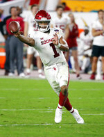 FILE - In this Dec. 29, 2018, file photo, Oklahoma quarterback Kyler Murray throws a pass during the second half of the Orange Bowl NCAA college football game against Alabama in Miami Gardens, Fla. The Oakland Athletics remain hopeful of seeing Heisman Trophy winner Murray in their baseball uniform when spring training begins next month. While the Oklahoma quarterback declared for the NFL draft last week, the prized outfielder could report to A's spring training in Mesa, Arizona--and he has an invite to big league camp. (AP Photo/Wilfredo Lee, File)
