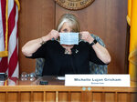 FILE - In this April 15, 2020, file photo, New Mexico Gov. Michelle Lujan Grisham puts on her face mask when not speaking during an update on the COVID-19 outbreak in the state during a news conference in the state Capitol in Santa Fe, N.M. New Mexico Republicans and sheriffs are asking U.S. Attorney General William Barr to look into Gov. Michelle Lujan Grisham's health orders aimed at stopping the spread of COVID-19. They allege the order, which has closed several small businesses, violates residents' civil rights. (Eddie Moore/The Albuquerque Journal via AP, Pool, File)