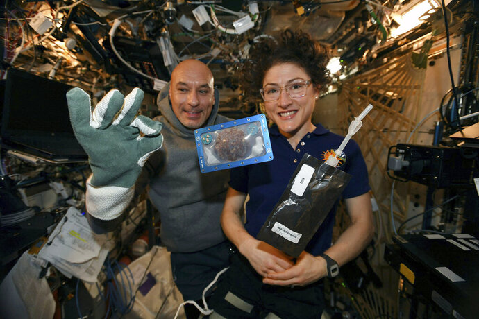 In this photo made available by U.S. astronaut Christina Koch via Twitter on Dec. 26, 2019, she and Italian astronaut Luca Parmitano pose for a photo with a cookie baked on the International Space Station. The results are finally in for the first chocolate chip cookie bake-off in space. While looking more or less normal, the best cookies required two hours of baking time last month up at the International Space Station. It takes far less time on Earth, under 20 minutes. And how do they taste? No one knows. (NASA via AP, File)