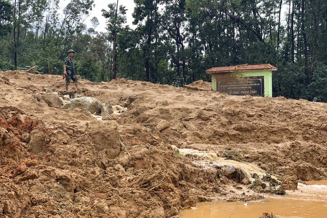 An army officer stands at the site of a landslide at a forest ranger outpost in Thua Thien-Hue province, Vietnam, Thursday, Oct. 15, 2020. Rescuers recovered the bodies of 11 army personnel and two other people who were buried in the landslide while trying to reach victims of another landslide, state media reported Friday, Oct. 16, 2020. (Tran Le Lam/VNA via AP)