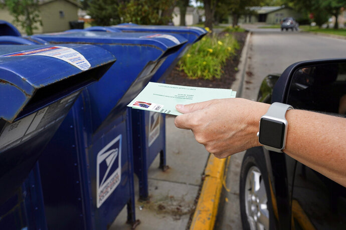 FILE - In this Tuesday, Aug. 18, 2020, file photo, a person drops applications for mail-in-ballots into a mailbox in Omaha, Neb. Data obtained by The Associated Press shows Postal Service districts across the nation are missing the agency's own standards for on-time delivery as millions of Americans prepare to vote by mail. (AP Photo/Nati Harnik, File)