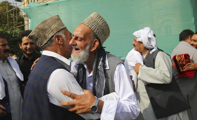 Afghan Muslims greet each other after offering Eid al-Adha prayers in Kabul, Afghanistan, Sunday, Aug. 11, 2019. Muslim people in the country celebrate Eid al-Adha, or the Feast of the Sacrifice by slaughtering sheep, goats and cows whose meat will later be distributed to the poor.(AP Photo/Rafiq Maqbool)