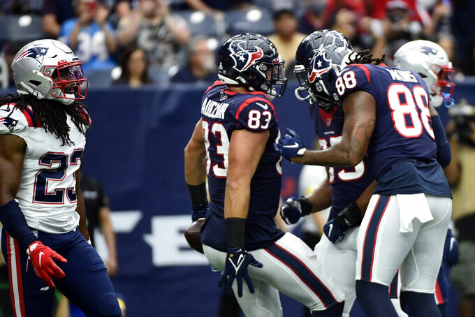Houston Texans tight end Antony Auclair (83) celebrates with Jordan Akins (88) and Pharaoh Brown after catching a pass for a touchdown as New England Patriots safety Kyle Dugger (23) walks past during the first half of an NFL football game Sunday, Oct. 10, 2021, in Houston. (AP Photo/Justin Rex)