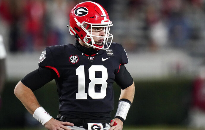 Georgia quarterback JT Daniels looks for a play call from the sideline during the first half of the team's NCAA college football game against Mississippi State, Saturday, Nov. 21, 2020, in Athens, Ga. (AP Photo/Brynn Anderson)