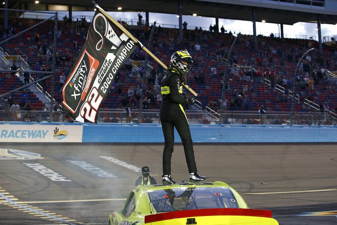 Austin Cindric stands on the roof of his race car holding a season champion banner after winning the NASCAR Xfinity Series auto race at Phoenix Raceway, Saturday, Nov. 7, 2020, in Avondale, Ariz. (AP Photo/Ralph Freso)
