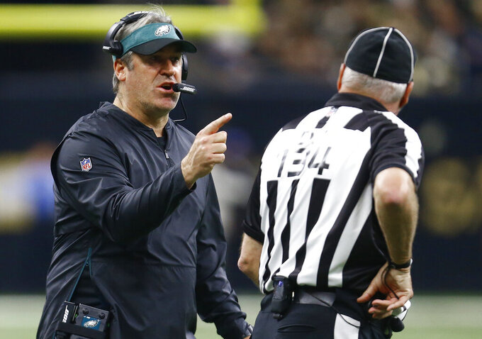 Philadelphia Eagles head coach Doug Pederson speaks with head linesman Ed Camp (134) in the first half of an NFL divisional playoff football game against the New Orleans Saints, in New Orleans, Sunday, Jan. 13, 2019. (AP Photo/Butch Dill)