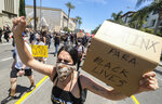 A woman holds a sign during a protest over the death of George Floyd in Los Angeles, Saturday, May 30, 2020. Protests across the country have escalated over the death of George Floyd who died after being restrained by Minneapolis police officers on Memorial Day, May 25. (AP Photo/Ringo H.W. Chiu)