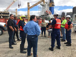 In this photo provided by the U.S. Coast Guard, U.S. Coast Guard members and other local agency personnel discuss clean-up operations of the impacted areas after an oil discharge from vessel Kamokuiki at Pier 19 in Honolulu, Thursday, Nov. 7, 2019. Two response vessels arrived on scene and deployed 1,600 feet of hard boom surrounding the 25 bales of absorbent material. (Petty Officer 2nd Class James Connor/U.S. Coast Guard via AP)