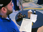 This March 8, 2019 photo shows a gambler preparing his bets on the first day of the March Madness college basketball tournament at the Borgata casino in Atlantic City N.J. Figures released by state gambling regulators on Thursday, April 25, 2019 show more than $106 million was wagered on the NCAA basketball championship tournament in New Jersey _ three times the amount wagered on the Super Bowl. (AP Photo/Wayne Parry)