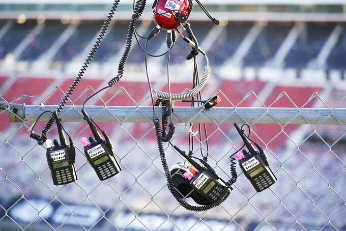 A spotter's radios hang on a fence on the roof of Bristol Motor Speedway before a NASCAR Xfinity Series auto race at Friday, Sept. 17, 2021, in Bristol, Tenn. (AP Photo/Mark Humphrey)