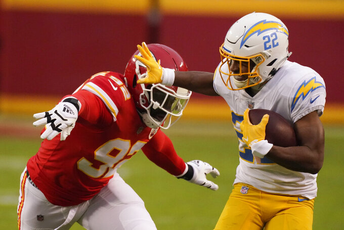 Los Angeles Chargers running back Justin Jackson run from Kansas City Chiefs defensive end Tanoh Kpassagnon, left, during the first half of an NFL football game, Sunday, Jan. 3, 2021, in Kansas City. (AP Photo/Charlie Riedel)