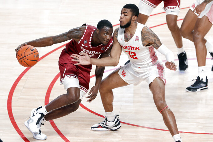 Temple forward De'Vondre Perry, left, drives around Houston forward Reggie Chaney (32) during the second half of an NCAA college basketball game Tuesday, Dec. 22, 2020, in Houston. (AP Photo/Michael Wyke)