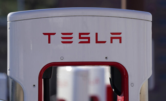 FILE - The company logo is shown at the top of a supercharger for Tesla automobiles near shops Feb. 25, 2021 in Boulder, Colo. Tesla's quarterly profit has surpassed $1 billion for the first time thanks to the electric car pioneer's ability to navigate through a pandemic-driven computer chip shortage that has caused major headaches for other automakers. The financial milestone announced Monday, July 26, 2021 extended a two-year run of prosperity that has erased questions about Tesla's long-term viability raised during its early years of losses and production problems. (AP Photo/David Zalubowski, file)