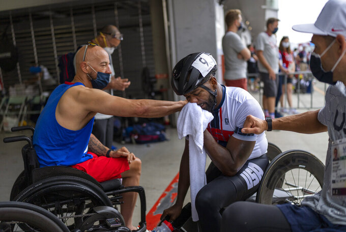 """Freddie De Los Santos, is comforted by Tom Davis, left, after losing in the Men's H5 Road Race at the Fuji International Speedway at the Tokyo 2020 Paralympics, on Wednesday, Sept. 1, 2021, in Tokyo, Japan. De Los Santos says combat taught him to thrive on pain, making him a relentless competitor. """"You enjoy the pain,"""" he said. """"Sometimes, that pain is your best enemy. When I'm racing and I start to feel the pain, I say 'How are you doing?'"""" (AP Photo/Emilio Morenatti)"""