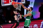 Boston Celtics forward Jayson Tatum, right, dunks the ball as Miami Heat's Tyler Herro, left, defends during the first half of an NBA conference final playoff basketball game, Saturday, Sept. 19, 2020, in Lake Buena Vista, Fla. (AP Photo/Mark J. Terrill)