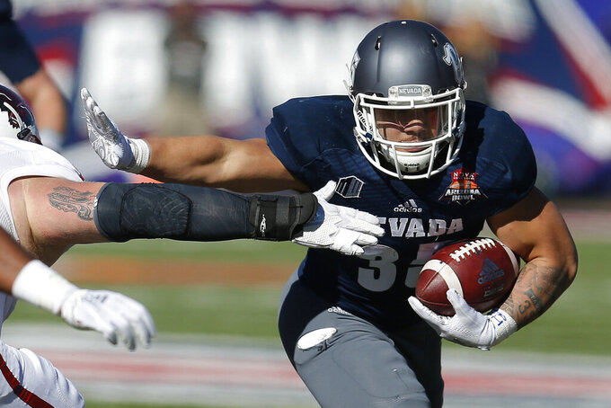 FILE - In this Dec. 29, 2018, file photo, Nevada running back Toa Taua (35) carries against Arkansas State in the first half of an NCAA college football in Tucson, Ariz. Purdue receiver Rondale Moore and Nevada running back Toa Taua each made a big mark on his respective team as a freshman. Now it's time to see what they'll do for an encore, beginning Friday night when Nevada hosts Purdue in the season opener for both teams. (AP Photo/Rick Scuteri, File)