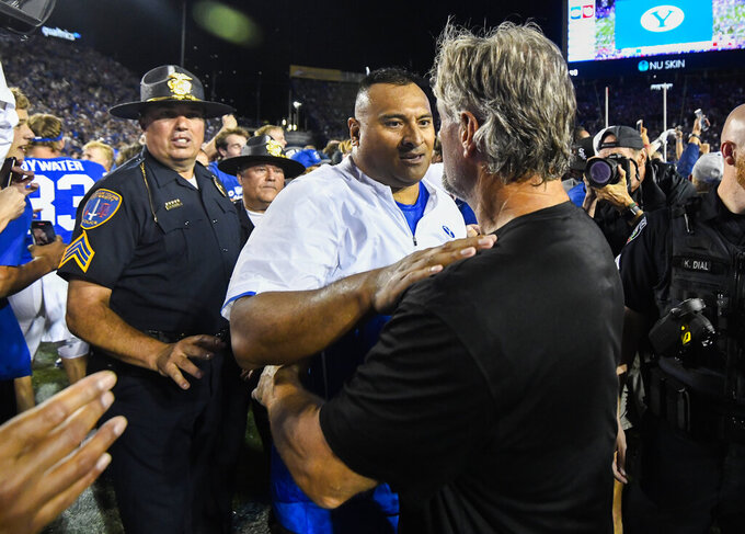 Brigham Young head coach Kalani Sitake, left, shakes the hand of Utah head coach Kyle Whittingham, right, after a NCAA college football game Saturday, Sept. 11, 2021, in Provo, Utah. (AP Photo/Alex Goodlett)