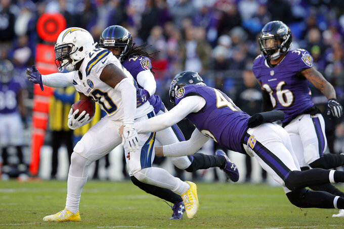 Los Angeles Chargers defensive back Desmond King, left, rushes past Baltimore Ravens cornerback Maurice Canady, from left, long snapper Morgan Cox and defensive back Chuck Clark in the second half of an NFL wild card playoff football game, Sunday, Jan. 6, 2019, in Baltimore. (AP Photo/Carolyn Kaster)