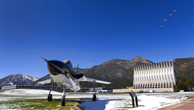 Four F-35A fighter jets fly over the Air Force Academy in Colorado Springs, Colo., Friday, April 17, 2020, to honor the Class of 2020 who will graduate early in a closed ceremony Saturday on the terrazzo at the center of campus rather than Falcon Stadium. The early graduation on the terrazzo will allow them to stay 8 feet apart during the COVID-19 pandemic. Vice President Mike Pence will speak in person, but the cadets won't march up to receive diplomas and high fives and hugs are banned. The Thunderbirds will fly over at the conclusion of the ceremony that will be streamed online for families and friends. In the foreground is a Republic F-105D Thunderchief, the first supersonic tactical fighter-bomber developed from scratch. The first F-105D Thunderchief flew in 1959 and played a major role in the Vietnam War. (Christian Murdock/The Gazette via AP)