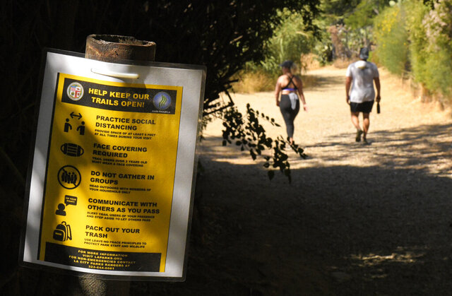 Hikers utilize the Innsdale Trail near the famed Hollywood Sign, Thursday, May 28, 2020, in Los Angeles. Several parks and trails have recently reopened in the city during the coronavirus pandemic. (AP Photo/Mark J. Terrill)