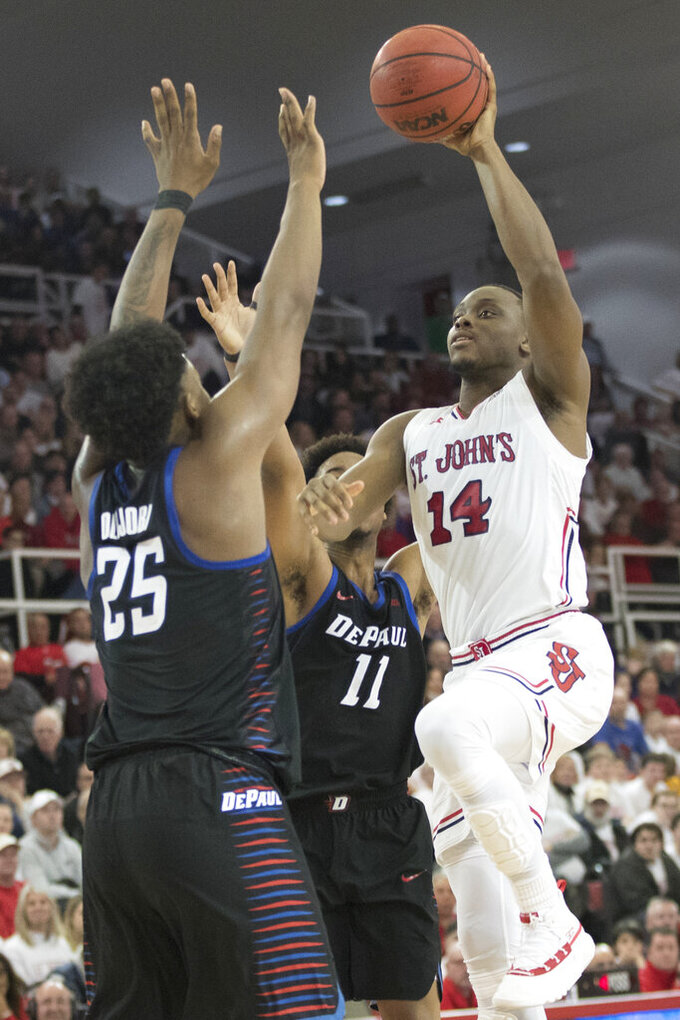 St. John's guard Mustapha Heron (14) goes to the basket against DePaul forward Femi Olujobi (25) and guard Eli Cain (11) in the second half of an NCAA college basketball game, Saturday, Jan. 12, 2019, in New York. DePaul won 79-71. (AP Photo/Mary Altaffer)