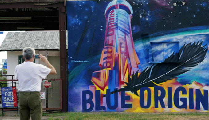 Gene Walker, of Denison, Texas, makes a photo of a Blue Origin mural on a building for sale in Van Horn, Texas, Tuesday Oct. 12, 2021. Today's launch has been pushed to Wednesday due to weather. (AP Photo/LM Otero)