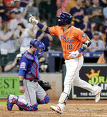 Houston Astros' Yuli Gurriel (10) points to the stands as he crosses home plate in front of Texas Rangers catcher Jeff Mathis on a home run during the second inning of a baseball game Friday, July 19, 2019, in Houston. (AP Photo/Michael Wyke)