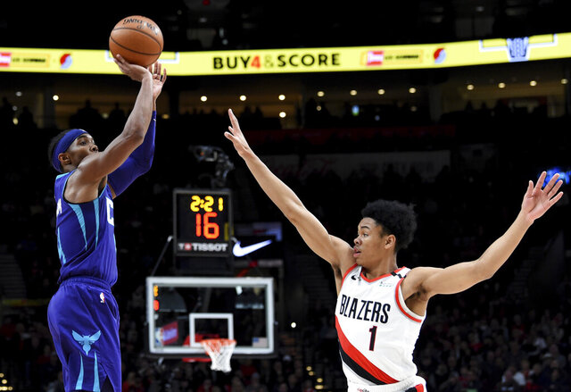 Charlotte Hornets guard Devonte' Graham, left, shoots the ball over Portland Trail Blazers guard Anfernee Simons, right, during the first half of an NBA basketball game in Portland, Ore., Monday, Jan. 13, 2020. (AP Photo/Steve Dykes)
