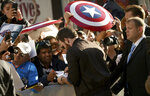 Chris Evans signs autograph as he attends the premiere for
