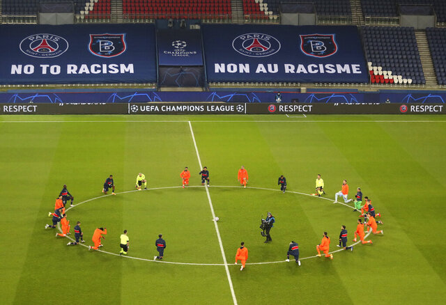 Basaksehir players kneel in support of the Black Lives Matter campaign before the start of the Champions League group H soccer match between Paris Saint Germain and Istanbul Basaksehir at the Parc des Princes stadium in Paris, France, Wednesday, Dec. 9, 2020. The match is resuming on Wednesday with a new refereeing team after players from Paris Saint-Germain and Istanbul Basaksehir left the field on Tuesday evening and didn't return when the fourth official — Sebastian Coltescu of Romania — was accused of using a racial term to identify Basaksehir assistant coach Pierre Webo before sending him off for his conduct on the sidelines. (Xavier Laine/Pool via AP)