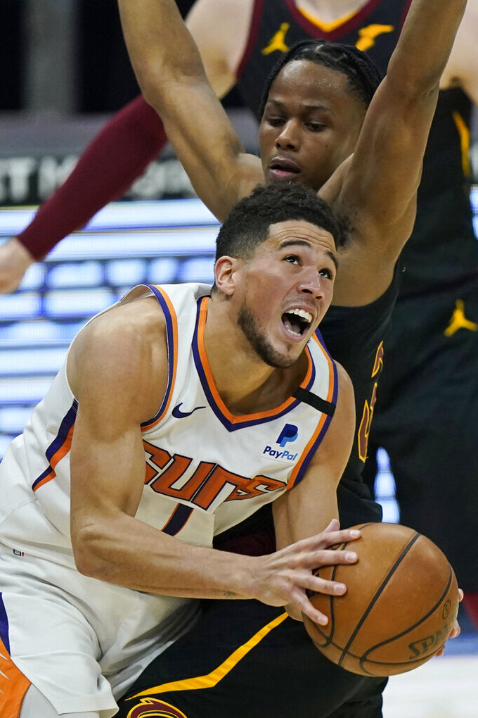 Phoenix Suns' Devin Booker (1) drives against Cleveland Cavaliers' Isaac Okoro (35) in the first half of an NBA basketball game, Tuesday, May 4, 2021, in Cleveland. (AP Photo/Tony Dejak)