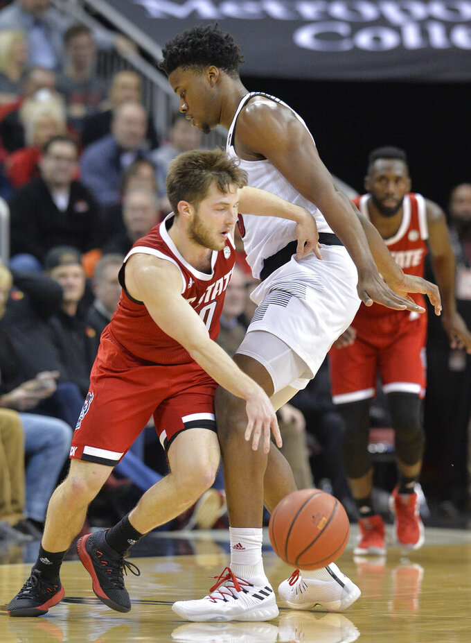 North Carolina State guard Braxton Beverly (10) nights his way around Louisville center Steven Enoch (23) during the second half of an NCAA college basketball game in Louisville, Ky., Thursday, Jan. 24, 2019. Louisville won 84-77. (AP Photo/Timothy D. Easley)