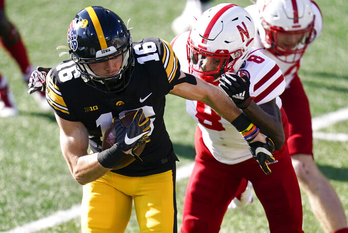 Iowa's Charlie Jones (16) runs from Nebraska's Deontai Williams (8) during a punt return in the first half of an NCAA college football game, Friday, Nov. 27, 2020, in Iowa City, Iowa. (AP Photo/Charlie Neibergall)