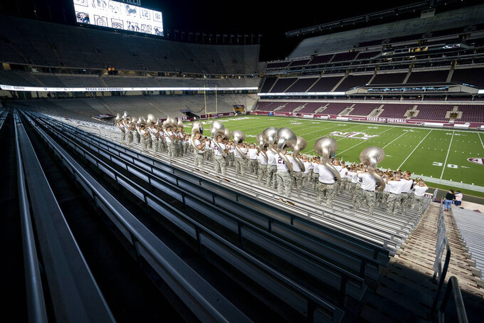 Members of the Texas A&M Corps of Cadets Band practice yells inside of Kyle Field as part of the first Midnight Yell Practice this season in College Station, Texas early Saturday, Sept. 26, 2020. Due to Coronavirus restrictions, the band was the only crowd allowed in the normally packed stands for the traditional game day event in College Station, Texas. (Sam Craft/Pool Photo via AP)