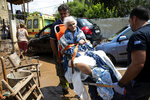 A woman is evacuated form her home by paramedics, following a storm at the village of Politika, on Evia island, northeast of Athens, on Sunday, Aug. 9, 2020. Five people have been found dead and dozens have been trapped in their homes and cars from a storm that has hit the island of Evia, in central Greece, police say. (AP Photo/Yorgos Karahalis)