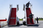 Members of the White House Military Office clean a stair for Air Force One ahead of the arrival of President Donald Trump at Lehigh Valley International Airport, Thursday, May 14, 2020, in Allentown, Pa. (AP Photo/Evan Vucci)