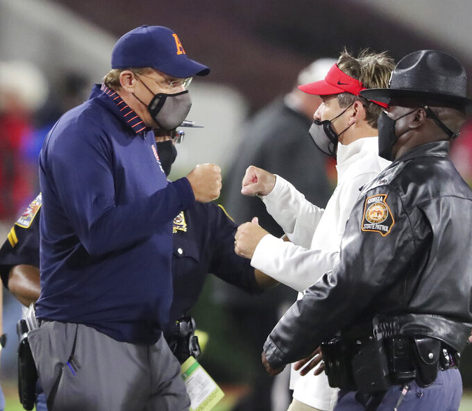 Auburn coach Gus Malzahn, left, gives Georgia coach Kirby Smart a fist bump after Georgia defeated Auburn 27-6 in an NCAA college football game Saturday, Oct. 3, 2020, in Athens, Ga. (Curtis Compton/Atlanta Journal-Constitution via AP)