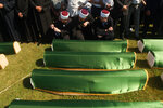 Relatives and friends of the victims, with religious leaders among the some thousands of mourners gathered at a soccer stadium in Kozarac near the town of Prijedor, behind the coffins draped with green cloth for the funeral of 86 Muslims, Saturday July 20, 2019.  The victims were slain by Serbs in one of the worst atrocities of the country's 1992-95 war, aged 19 to 61, and were among some 200 Bosnian Muslims and Croats from Prijedor who were executed in Aug. 1992 on a cliff on Mt. Vlasic known as Koricanske Stijene. (AP Photo/Almir Alic)