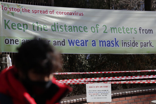 A man wearing a face mask walks past a banner for a precaution against the coronavirus in Seoul, South Korea, Wednesday, Dec. 16, 2020. (AP Photo/Lee Jin-man)