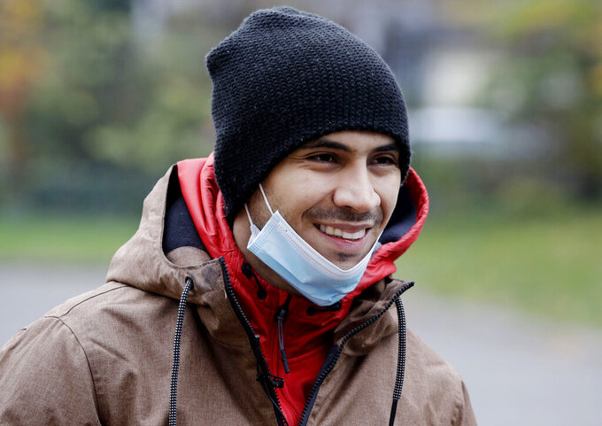 Venezuela's 2012 Olympic champion in fencing, Ruben Limardo Gascon, takes off his mask to pose for a photo during a short break from his job of delivering food for Uber Eats in Lodz, Poland, Saturday, Nov. 14, 2020. In Poland, where he has lived for years, GAscon delivers food for Uber Eats to support his family as he trains for the Olympics in Tokyo next summer(AP Photo/Czarek Sokolowski)