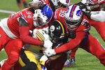Pittsburgh Steelers running back James Conner (30) is gang tackled by Buffalo Bills defensive tackle Vernon Butler (94) and Harrison Phillips (99) during the first half of an NFL football game in Orchard Park, N.Y., Sunday, Dec. 13, 2020. (AP Photo/Adrian Kraus)