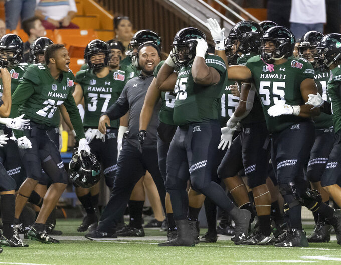 Hawaii players and coaches celebrate a fumble recovery by Hawaii defensive lineman Kendall Hune (95) in the first half of the Hawaii Bowl NCAA college football game against Louisiana Tech, Saturday, Dec. 22, 2018, in Honolulu. (AP Photo/Eugene Tanner)